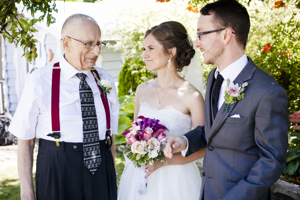 bride and groom with grandfather after wedding ceremony