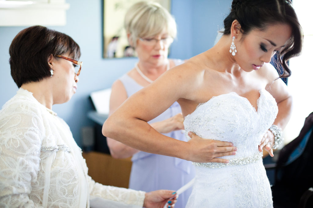 mothers helping bride into wedding dress