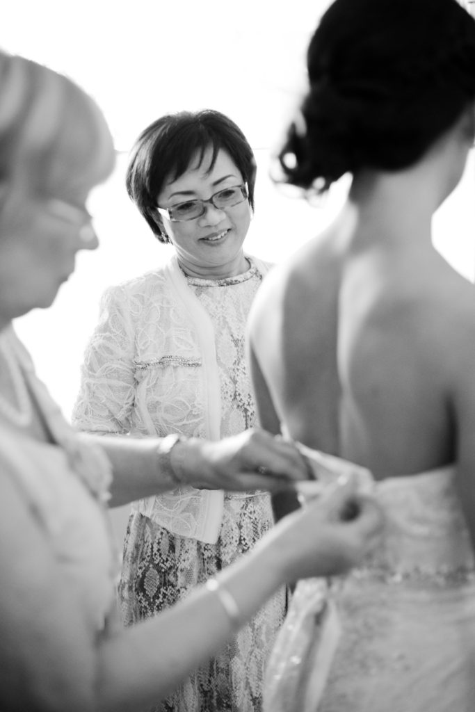 mother of the bride watching as bride gets dress on