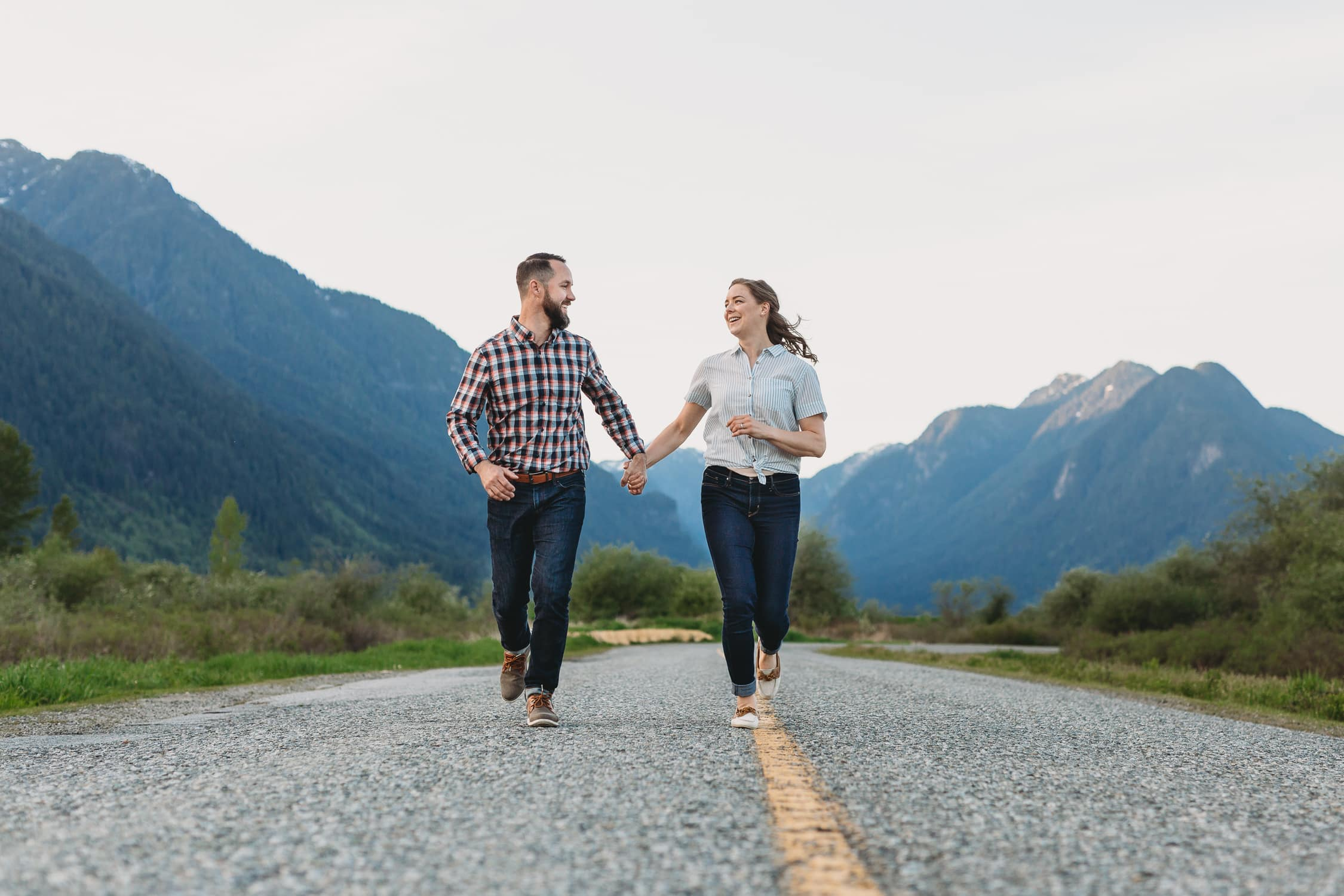 fun couples session fraser valley running down the road with mountain backdrop