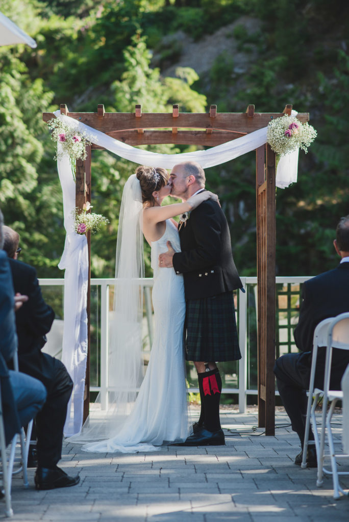 Wedding ceremony first kiss with groom in Scottish kilt
