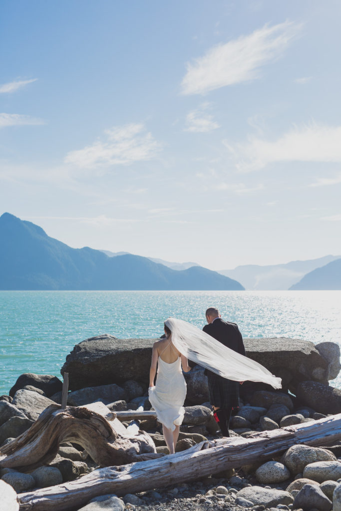 Wedding photojournalist, couple walking on rocks by the ocean at Furry Creek wedding
