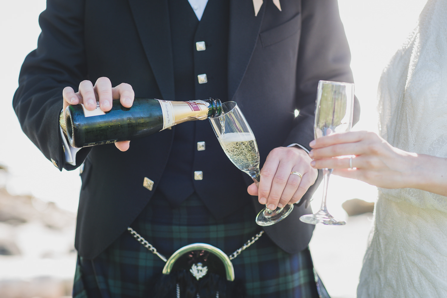 groom in kilt with champagne