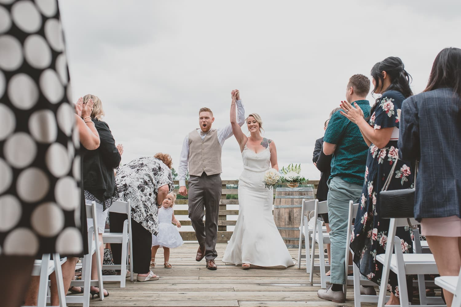 couple coming down the aisle after wedding ceremony on dock at south bonson community centre