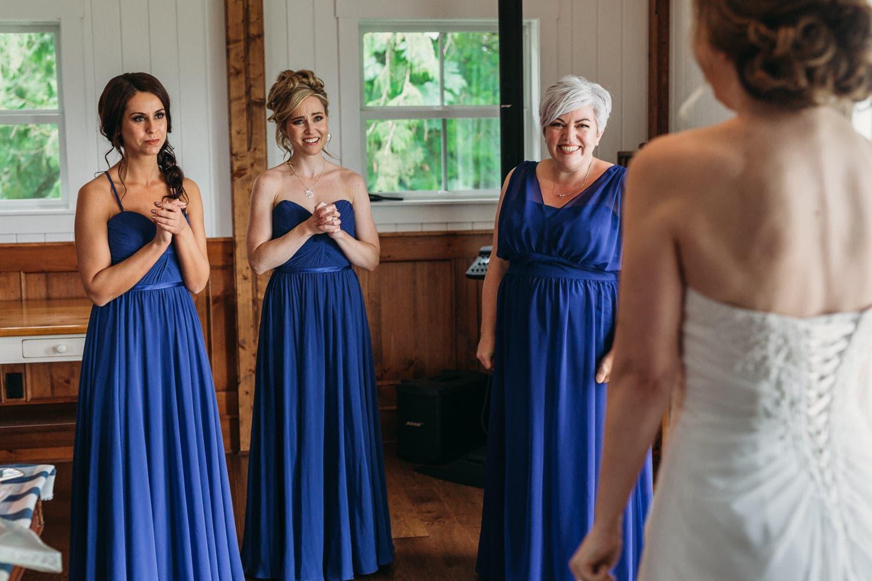 excited bridesmaids seeing bride at heronsbridge getting ready suite