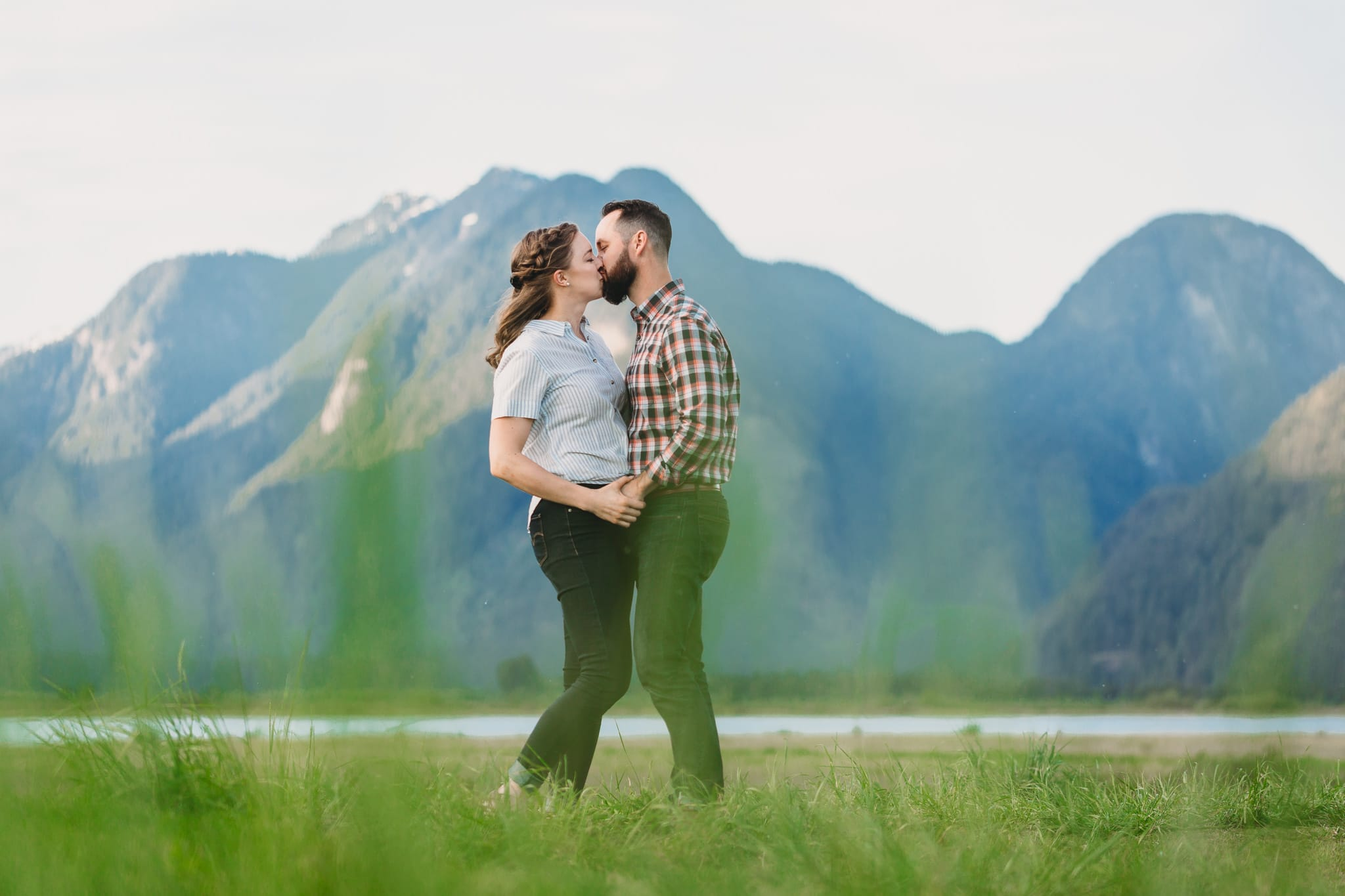 couple kissing at pitt lake engagement session with mountains in background