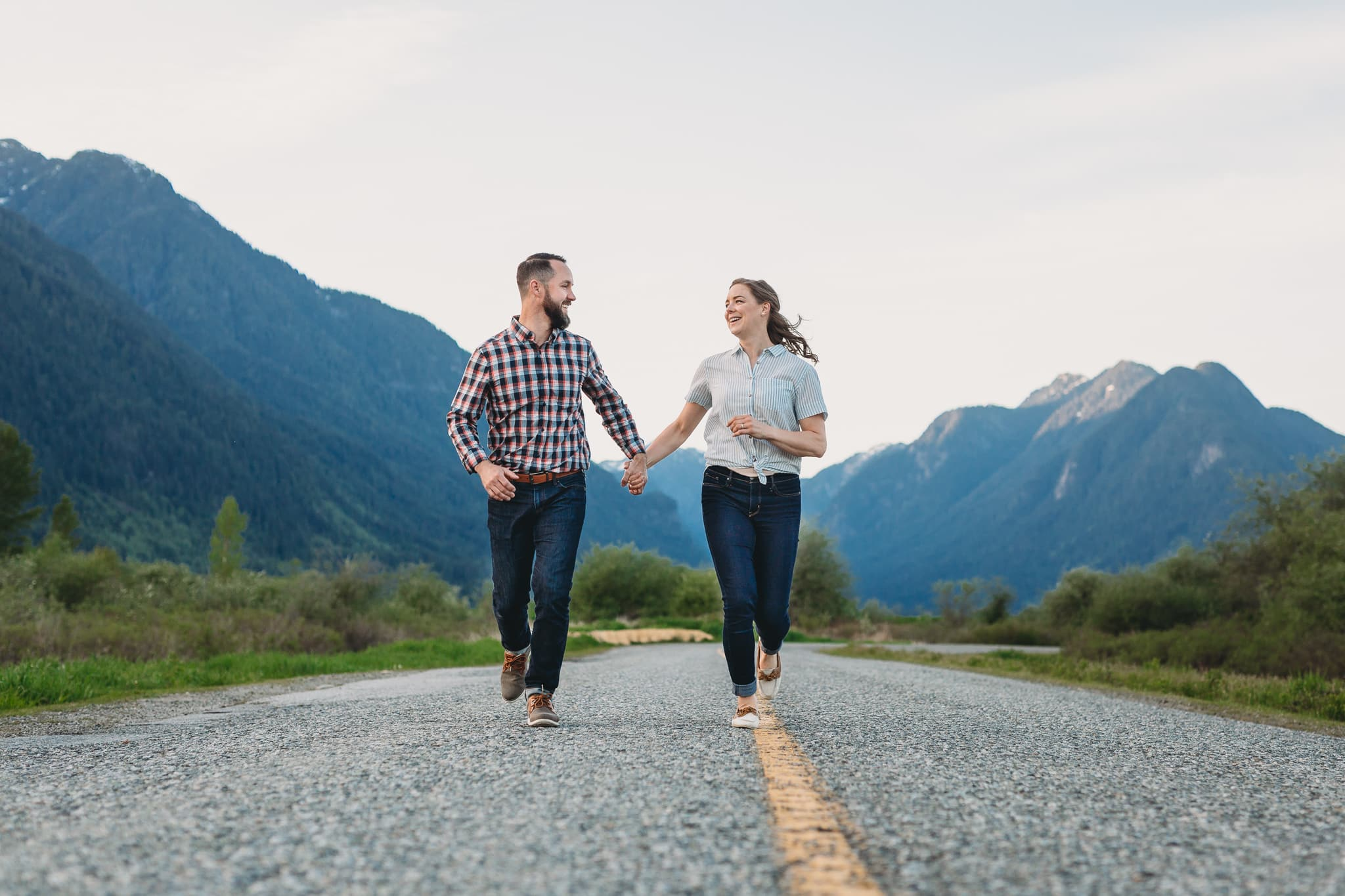 couple running down the road in pitt meadows at offbeat engagement session